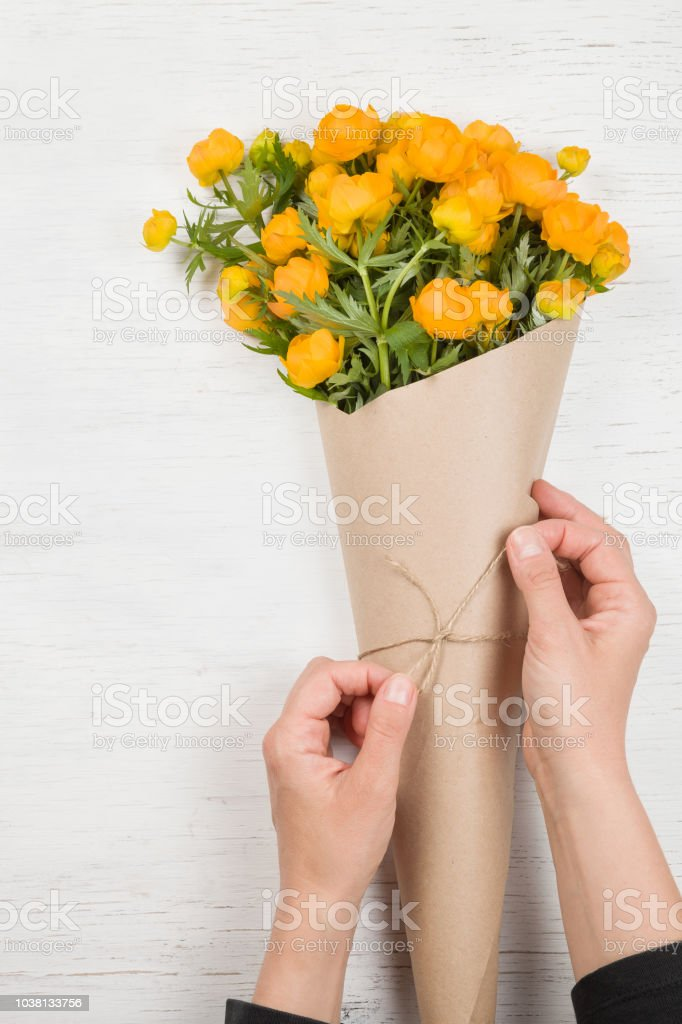 Young woman making a bouquet of yellow flowers. Top view on girl\'s...