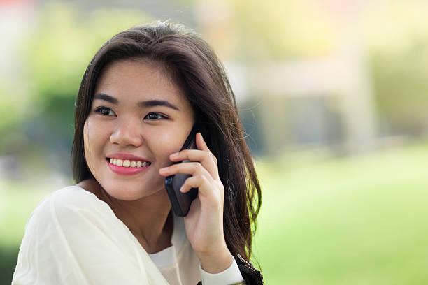 young woman making a call with her phone - philippines girl stock photos and pictures