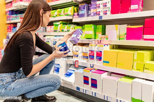 istock Young woman making a choice of sanitary pads 1088349846