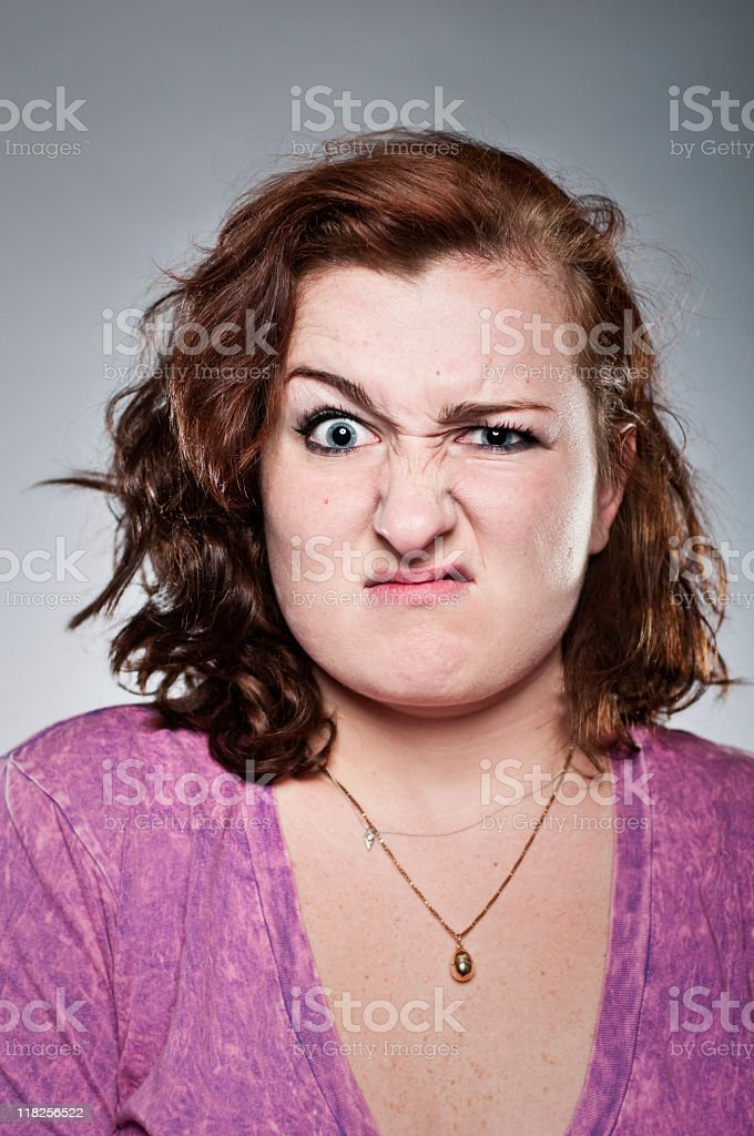 Young woman making a face on a grey background stock photo