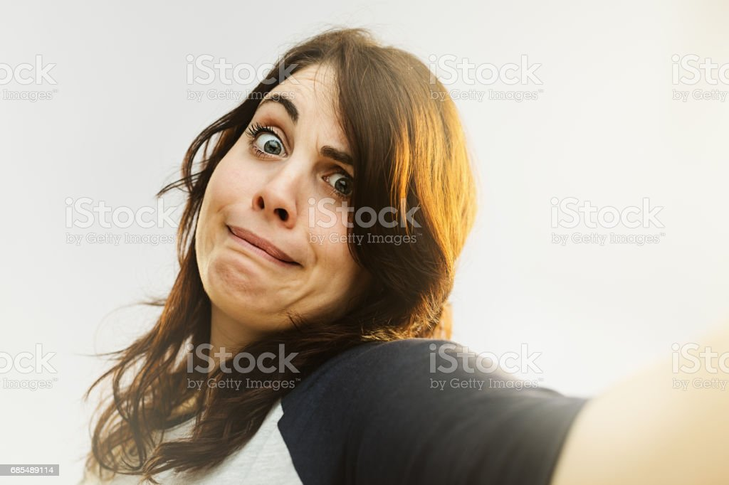 Young woman making a funny face and taking selfie stock photo