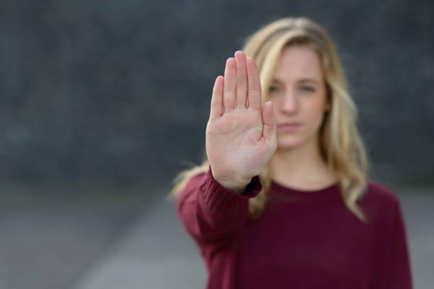 mujer joven haciendo un gesto de alto - stop sign fotografías e imágenes de stock