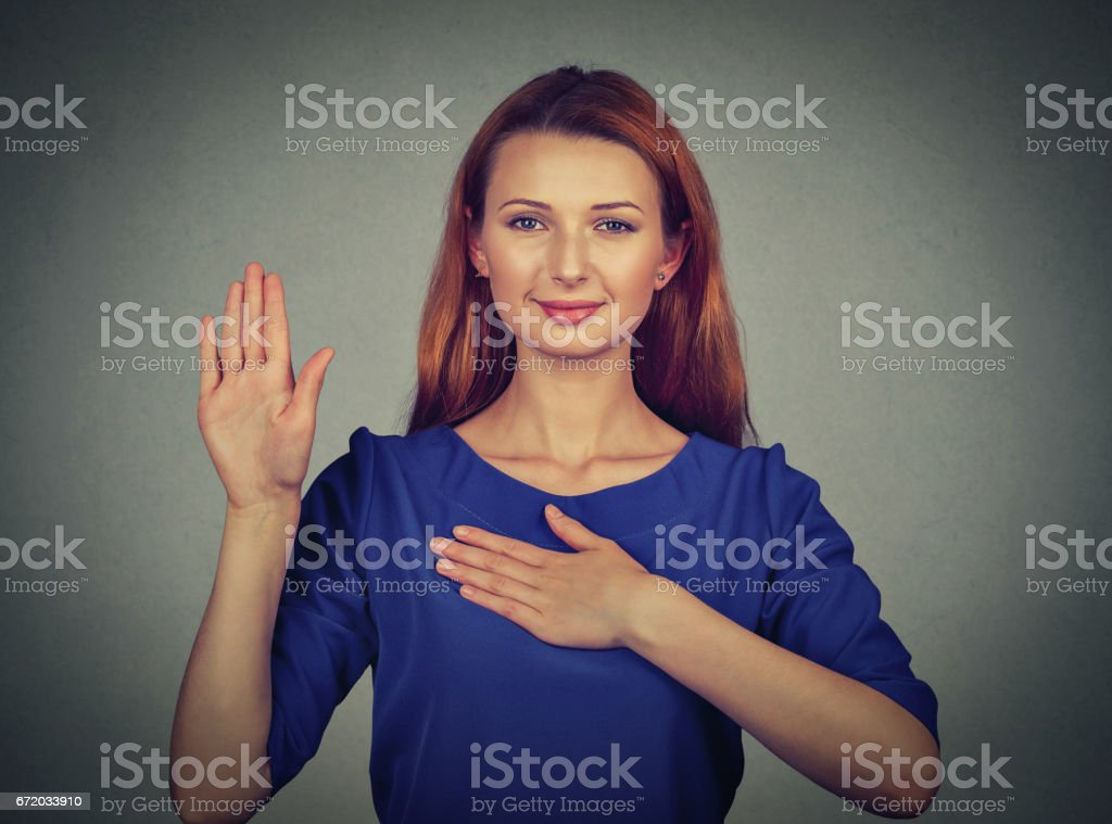 Young woman making a promise isolated on gray wall background stok fotoğrafı