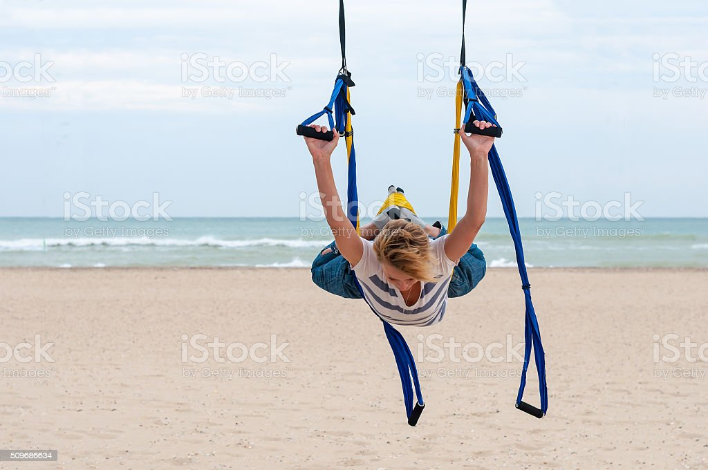 Young woman making antigravity yoga. fly-yoga exercises with yellow stock photo