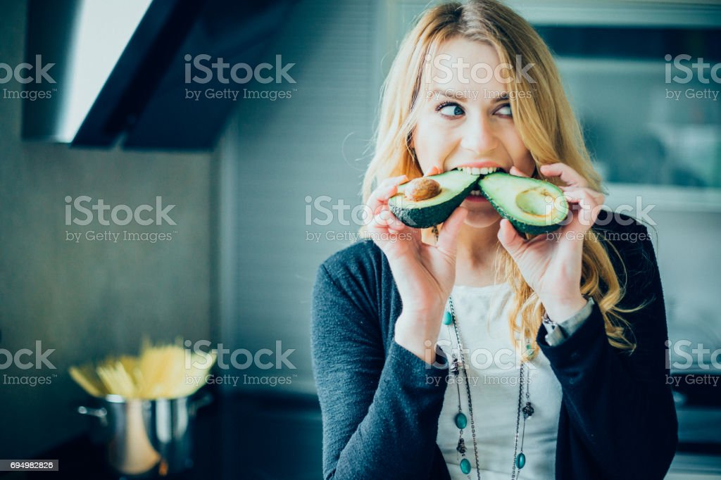 Young woman making avocado meal in the kitchen stock photo