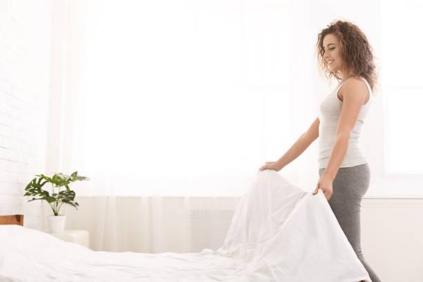 young woman making bed and organizing room - sheet imagens e fotografias de stock