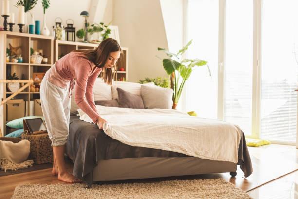 Junge Frau macht zu Hause Bett – Foto
