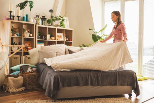 young woman making bed at home - украшать стоковые фото и изображения