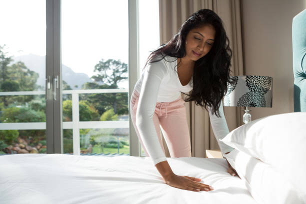 Young woman making bed at home stock photo