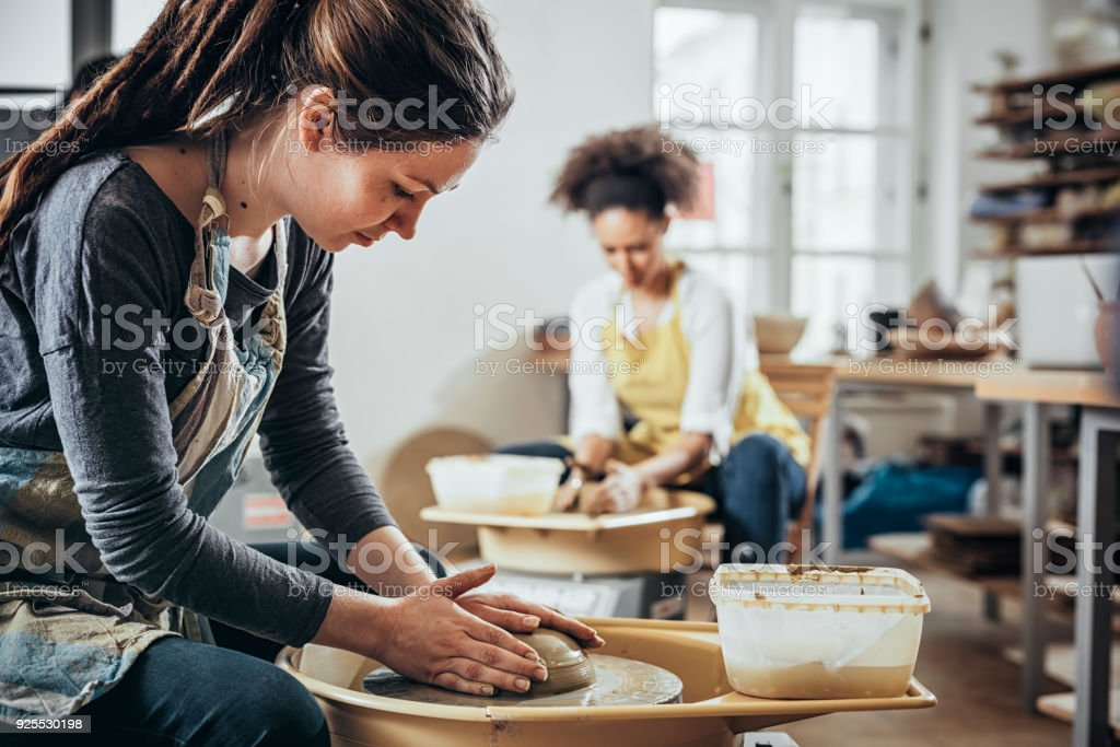 Young Woman making ceramic work with potter's wheel stock photo