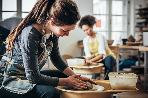 Young Woman making ceramic work with potter's wheel