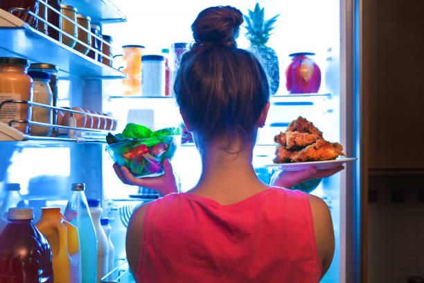 年輕女人做出的選擇健康的沙拉或垃圾食品炒雞 - 不健康飲食 個照片及圖片檔
