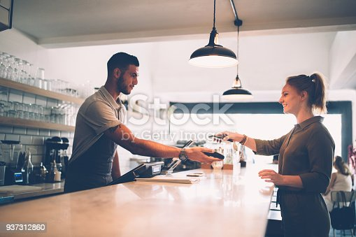 Young hipster woman paying though NFC smartphone technology at modern coffee shop