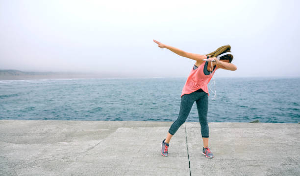 Young woman making dab dance outdoors stock photo