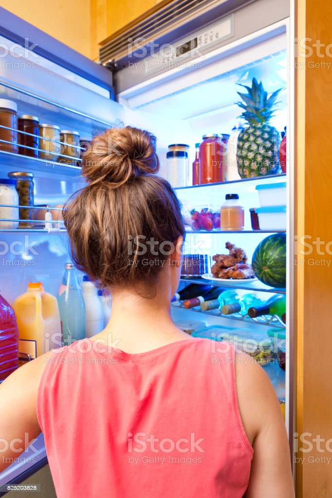Young Woman Making Decision on Healthy Eating in Front of Refrigerator stock photo