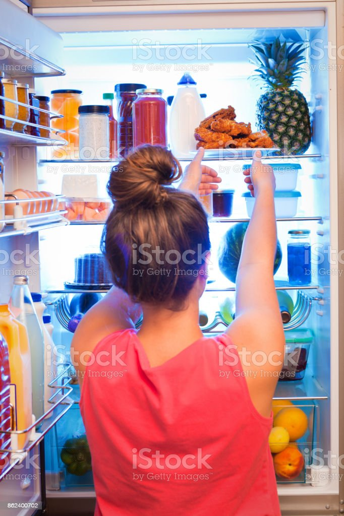 Young Woman Making Decision on Unhealthy Eating in Front of Refrigerator stock photo
