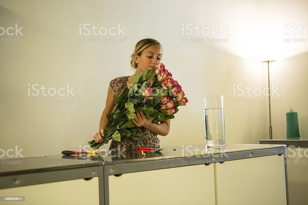 Young attractive woman taking care of roses in a retail...