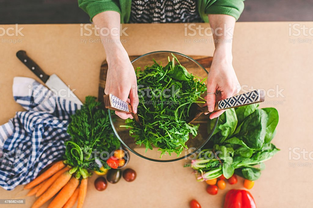Young woman making fresh salad stock photo