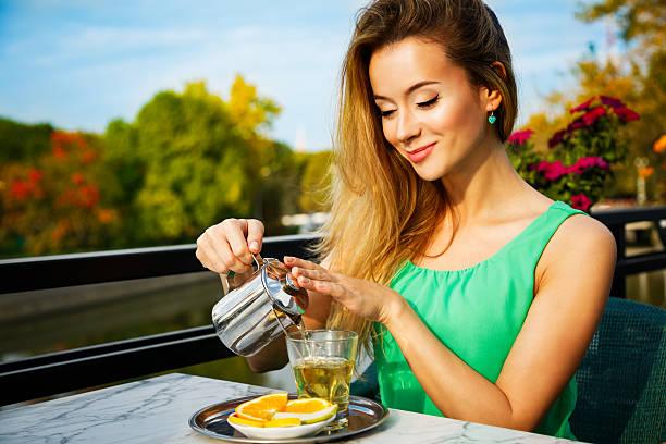 Junge Frau, die mit grünem Tee im Freien – Foto