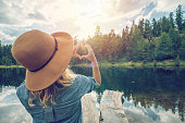 Young woman standing on lake pier makes a heart shape finger frame to show love and admiration to nature