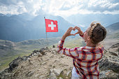 Young woman making heart shape finger frame on mountain top overlooking the Swiss Alps; Swiss flag