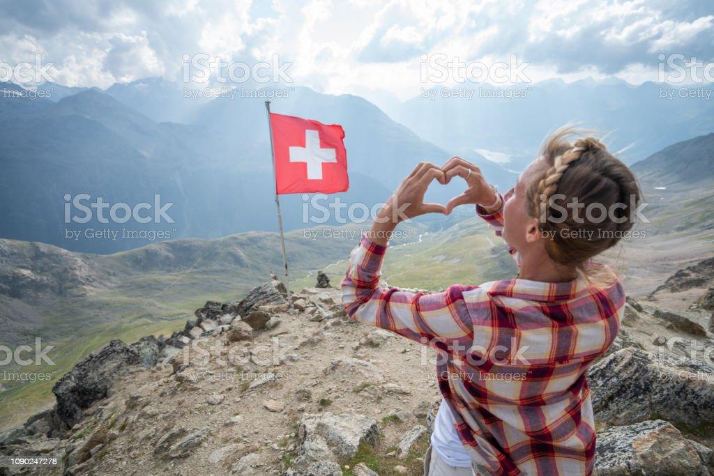 Junge Frau macht Herz Form Finger Frame auf Berggipfel mit Blick auf die Schweizer Alpen; Schweizer Flagge – Foto
