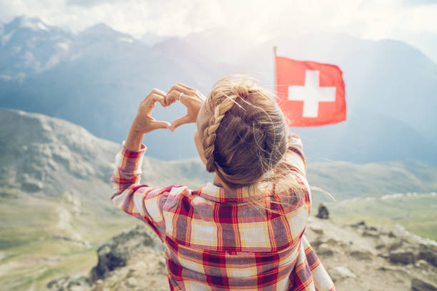 Young woman making heart shape finger frame on mountain top overlooking the Swiss Alps; Swiss flag stock photo