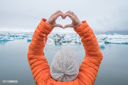 Young woman makes heart shape frame against glacier lake with icebergs floating. People travel exploration and climate change concept