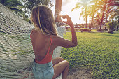 Young woman making heart shape finger frame relaxing on hammock in tropical climate loving serene environment with palm trees and green grass garden. People travel relax concept in vacations