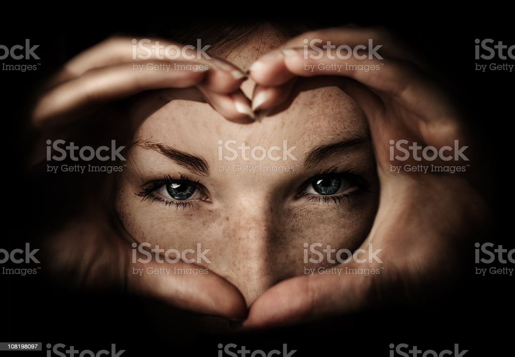 Young Woman Making Heart Shape with Hands stock photo