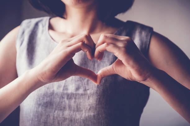 junge Frau macht ihre Hände in Herzform, Herzkrankenversicherung, soziale Verantwortung, Spenden-Charity-Konzept – Foto
