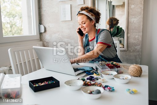 istock Young woman making jewelry and selling it online 1181284012