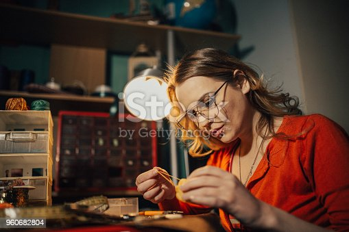 512345816istockphoto Young woman making jewelry indoors in the workshop 960682804