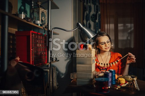 512345816istockphoto Young woman making jewelry indoors in the workshop 960682950