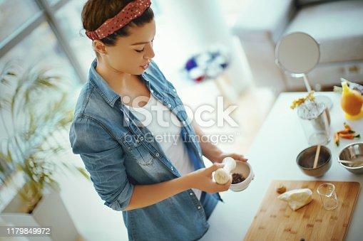 Young woman making organic natural face cream at her work.