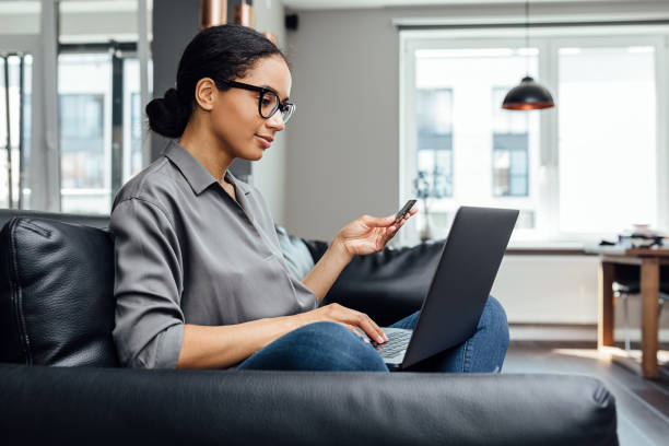 Young woman making online payment while sitting in the living room on sofa stock photo