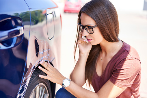 istock Young woman making phone call to insurance agent while inspecting scratched car 1040922168