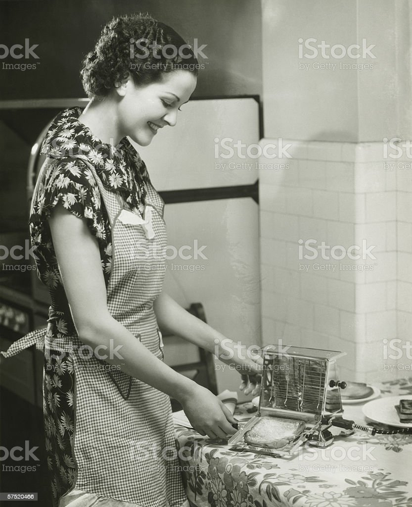 Young woman making slice of toast, (B&W), portrait stock photo
