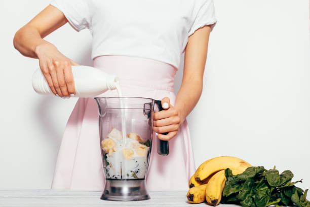 Young woman making spinach banana smoothie on white background Young woman making spinach banana smoothie on white background. She pouring milk in blender and mix ingredients together. Simple elegant picture with copy space. blender stock pictures, royalty-free photos & images