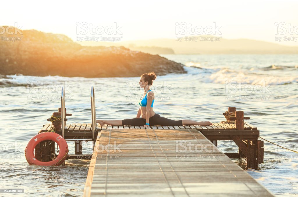 Young woman making splits on a pier stock photo