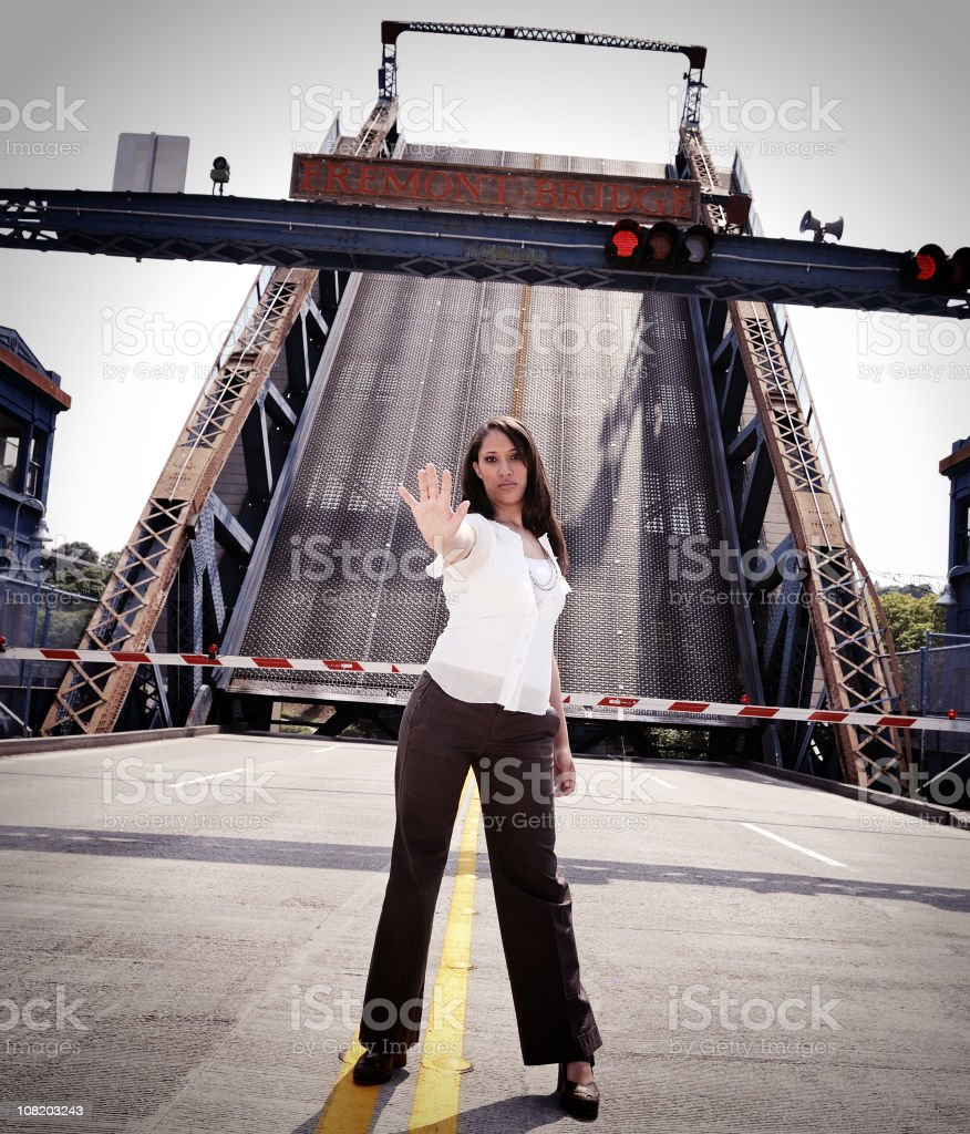 Young Woman Making Stop Gesture on Draw Bridge stock photo