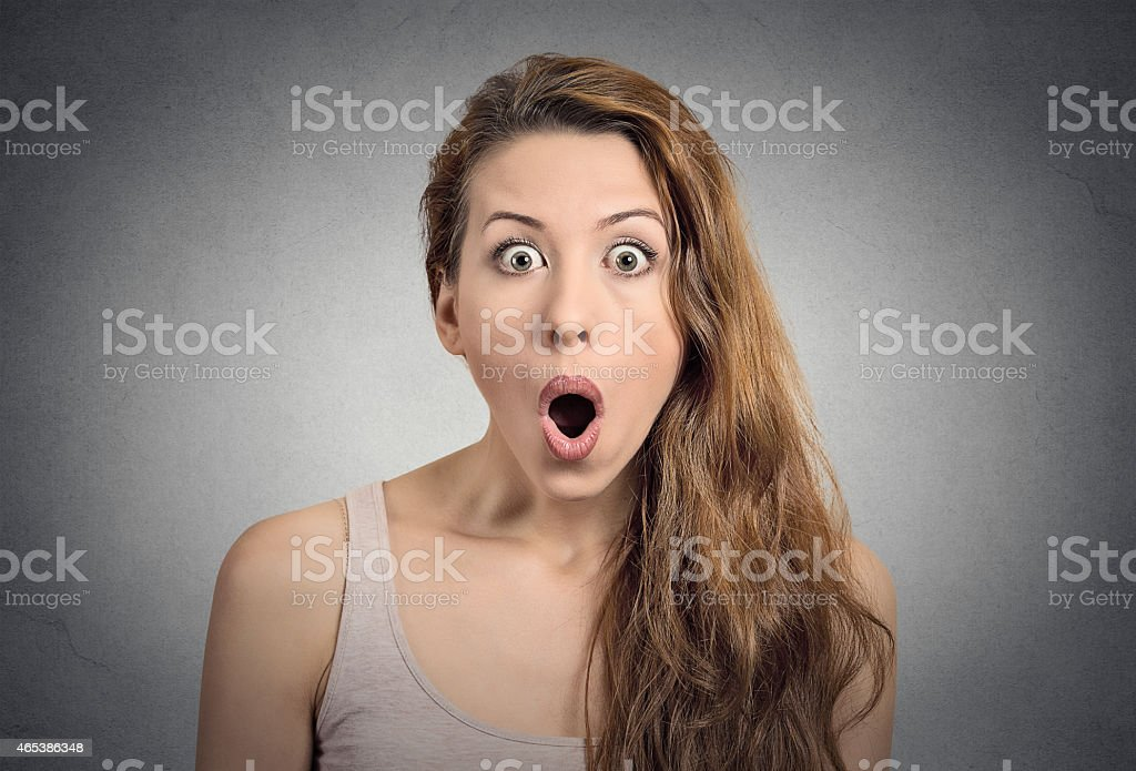 Young woman making surprised face on grey background stock photo