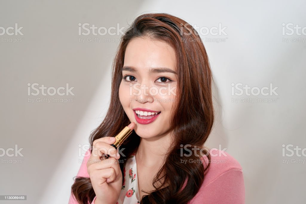 Young woman making up with a lipstick