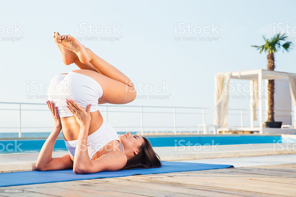 Young woman making yoga exercises stock photo