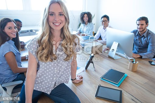 istock Young woman manager standing in front of her team. 476781218