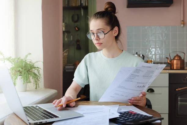 junge frau häusliche budget zu verwalten, mit offenen laptop, dokumente und rechner am küchentisch sitzen, mit touchpad, notizen mit bleistift - mieterhöhung stock-fotos und bilder
