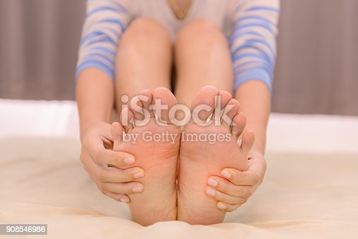901404510istockphoto Young woman massaging her feet on the bed., Healthcare concept 908546986
