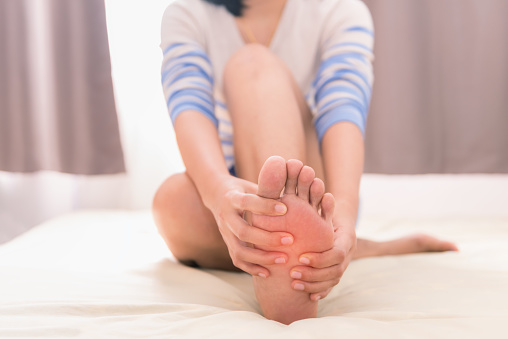 Young Woman Massaging Her Foot On The Bed Healthcare Concept Stock Photo - Download Image Now