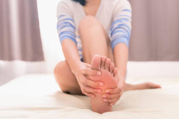 joven dando masajes a su pie en la cama, concepto salud - enfermedades de los pies fotografías e imágenes de stock