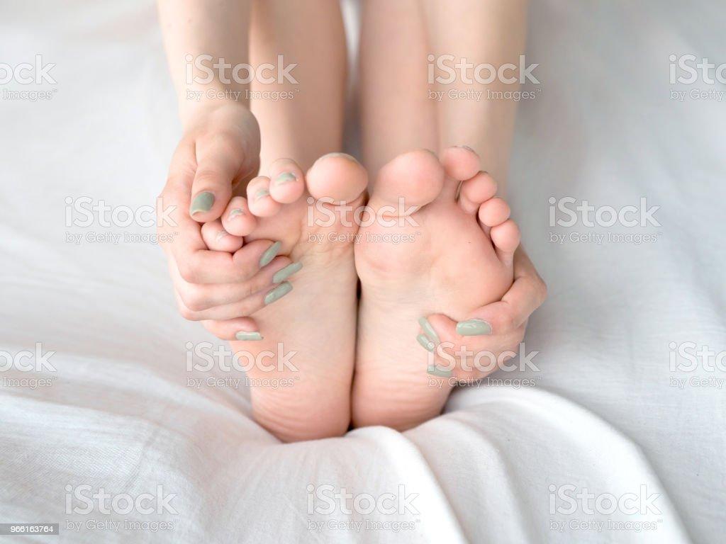 Ung kvinna massera hennes fot på sängen. Hälso-och koncept - Royaltyfri Asiatiskt och indiskt ursprung Bildbanksbilder